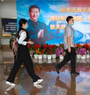 Gående framför en väggmålning av Kinas president Xi Jinping/Lastbil vid Scanias huvudkontot i Södertälje. TT
