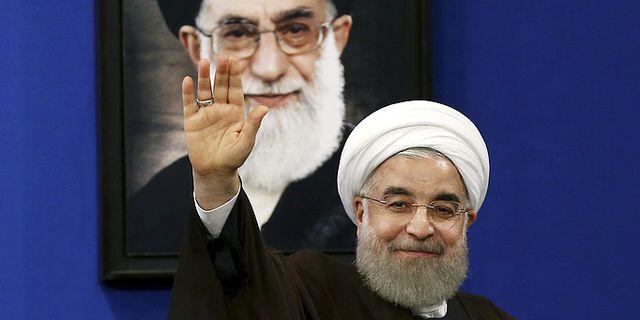 Irans president Hassan Rouhani vinkar under ett porträtt av Ayatollah Ali Khamenei. TT.
