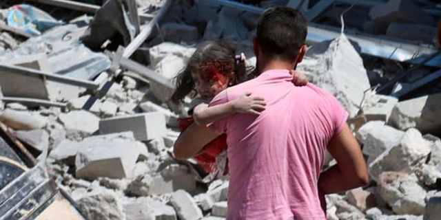 En man bär en skadad flicka i Ariha i Idlibprovinsen i Syrien. TT NYHETSBYRÅN/ NTB Scanpix