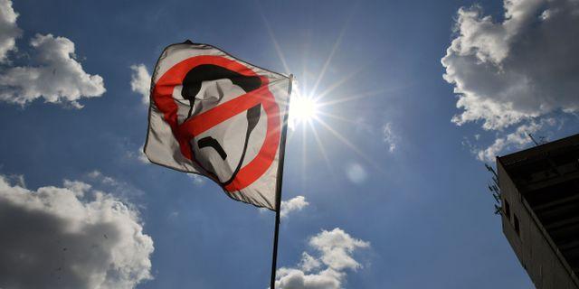 Protestflagga med en kryss över Maduros siluett. YURI CORTEZ / AFP