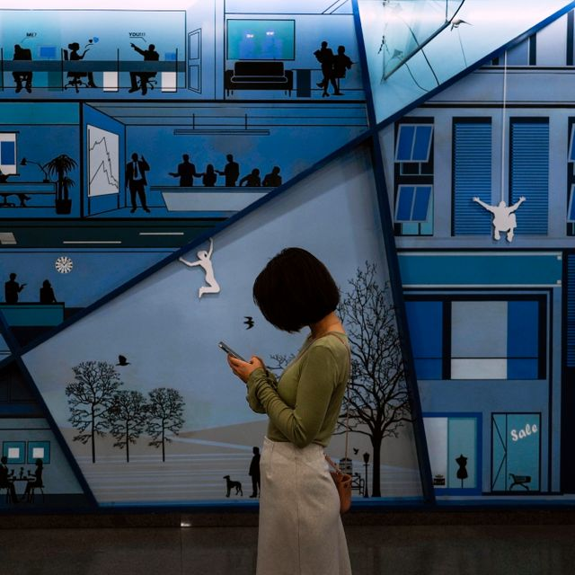 A woman browsing her smartphone in front of a billboard depicting office workers at a subway station in Beijing, Thursday, Sept. 16, 2021. Andy Wong / TT NYHETSBYRÅN