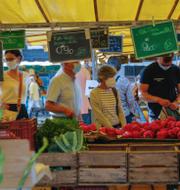 Människor besöker en matmarknad i franska Versailles/Bruno Le Maire. TT