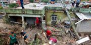 Boende i Ibrite i Minas Gerais städar upp efter översvämningarna. Alexandre Mota / TT NYHETSBYRÅN