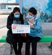 Två kvinnor i Pyongyang läser nyheter om att Kim Jong-Un tackar folket för deras uthållighet i ett tal på nyårsdagen.  Jon Chol Jin / TT NYHETSBYRÅN