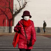 A woman wearing a mask to protect from the coronavirus cross a junction in Beijing on Wednesday, Jan. 20, 2021. Ng Han Guan / TT NYHETSBYRÅN