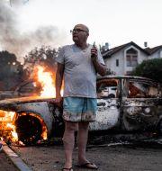 Jacob Simona vid sin brinnande bil i Lod, Israel. Bild från 11 maj. Heidi levine / TT NYHETSBYRÅN