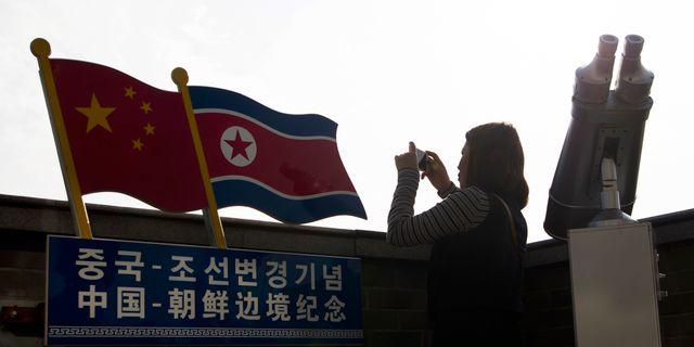 Arkivbild. Kvinna tar foto vid gränsen till Nordkorea i Jilinprovinsen.  TT NYHETSBYRÅN