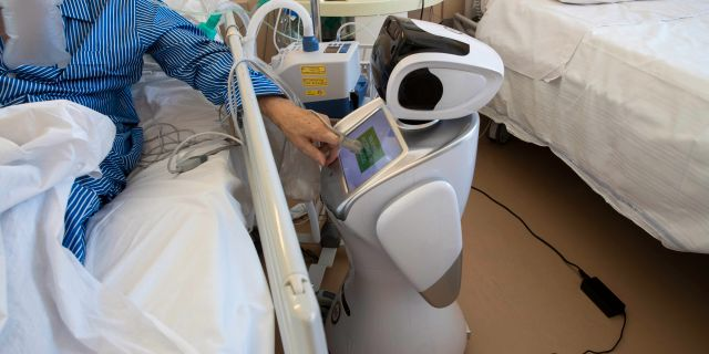 En covid-19-patient på ett sjukhus i Varese använder pekskärmen på en robot. Luca Bruno / TT NYHETSBYRÅN