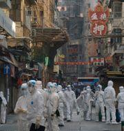 Regeringsanställda i skyddsutrustning går genom det nedstängda området i Hongkong.  Kin Cheung / TT NYHETSBYRÅN