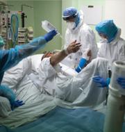 Olivier Véran och en person som vårdas på sjukhus. TT