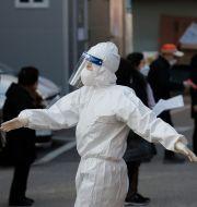 En sjukvårdare med skyddsutrustning i Seoul pratar med människor som står i kö för att testa sig. Lee Jin-man / TT NYHETSBYRÅN