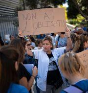 Vårdpersonal protesterar mot vaccintvånget. Daniel Cole / TT NYHETSBYRÅN