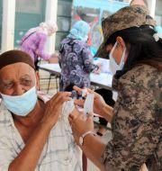 En soldat ger vaccin till en man i en skola utanför Tunis.  Hassene Dridi / TT NYHETSBYRÅN