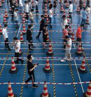 Fabriksarbetare i kö för att testa sig.  TT NYHETSBYRÅN