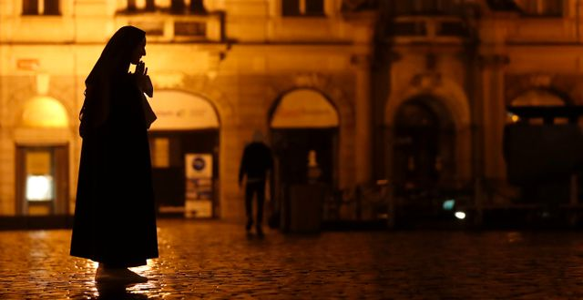 En nunna ber på ett i stort sett folktomt torg i Prags gamla stad Petr David Josek / TT NYHETSBYRÅN
