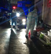 """Volontärer från gruppen """"Saimai Will Survive"""", vars arbete nämns i artikeln, hjälper en hemlös kvinna med covid-19 i Bangkok tidigare i veckan. Tassanee Vejpongsa / TT NYHETSBYRÅN"""