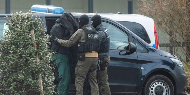En person förs in i rättsalen i Karlsruhe, Tyskland, efter razziorna mot den högerextrema grupperingen. Uli Deck / TT NYHETSBYRÅN