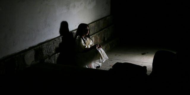 Susi, en av skådespelarna, väntar på en grupp turister som går på kyrkogårdstur. Dolores Ochoa / TT NYHETSBYRÅN