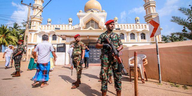 Polis utanför en kyrka i Negombo där oroligheter brutit ut.  STR / AFP