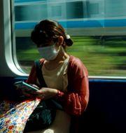 En kvinna i Tokyo kollar på sin telefon under en tågresa. Luca Bruno / TT NYHETSBYRÅN