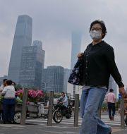 Fotgängare vid en tunnelbanestation i Peking med ansiktsmask för att skydda mot coronaviruset, på en bild från tidigare i juli. Andy Wong / TT NYHETSBYRÅN