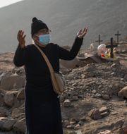 Kvinna sjunger vid sin mans grav i Peru.  Rodrigo Abd / TT NYHETSBYRÅN