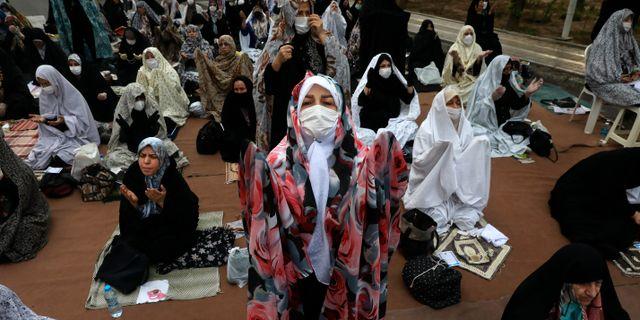 Kvinnor med munskydd ber om Guds hjälp att stoppa virusspridningen. Bilden är tagen utanför en moské i Irans huvudstad Teheran den 24 maj. Vahid Salemi / TT NYHETSBYRÅN