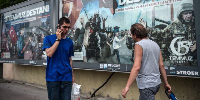 En man går förbi en affisch som satts upp i samband med högtidlighållandet av årsdagen sedan det misslyckade kuppförsöket.  OZAN KOSE / AFP
