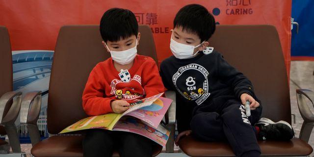Två pojkar i Hongkong bär ansiktsmasker för att skydda sig mot viruset. Kin Cheung / TT NYHETSBYRÅN