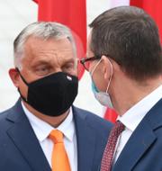 En EU-flagga och Ungerns premiärminister Viktor Orban och Polens premiärminister Mateusz Morawiecki.  TT