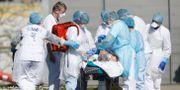Franska sjukvårdare hjälper en person. Jean-Francois Badias / TT NYHETSBYRÅN