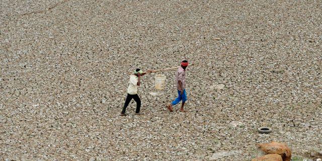 Indiska arbetare bär vatten från en uttorkad reservoar i Chennai. ARUN SANKAR / AFP