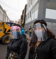 Två kvinnor i Lima som bär visir för att skydda sig mot smitta.  Rodrigo Abd / TT NYHETSBYRÅN