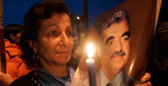 Arkivbild. En kvinna håller upp ett ljus framför en bild av den mördade tidigare premiärministern Rafik Hariri.  HUSSEIN MALLA / TT NYHETSBYRÅN
