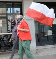 Människor i ansiktsmasker bär på en polsk flagga i Warszawa, Polen.  Czarek Sokolowski / TT NYHETSBYRÅN