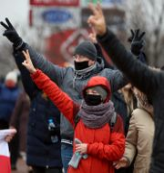 Personer som gör fredstecknet under söndagens demonstration i Minsk.  TT NYHETSBYRÅN