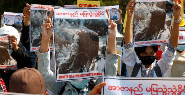 Demonstranter håller upp bilder på Mya Thwet Thwet Khine. TT NYHETSBYRÅN