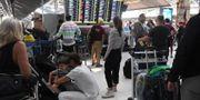 Strandsatta resenärer på flygplatsen i Bangkok.  LILLIAN SUWANRUMPHA / AFP