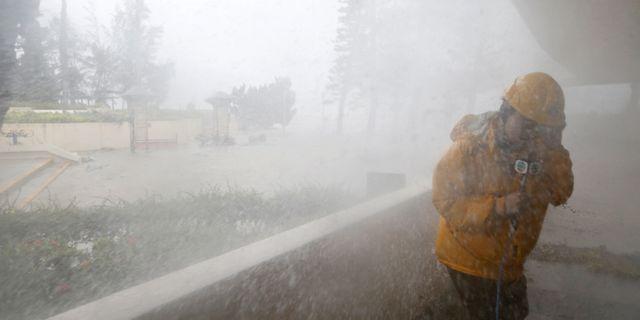En journalist hukar när stora vågor slår in vid Heng Fa Chuen, ett bostadsområde vid havet i Hongkong BOBBY YIP / TT NYHETSBYRÅN