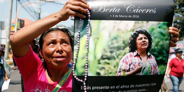 En kvinna håller upp ett fotografi av den mördade miljöaktivisten Berta Caceres  i Honduras. Fernando Antonio / TT / NTB Scanpix