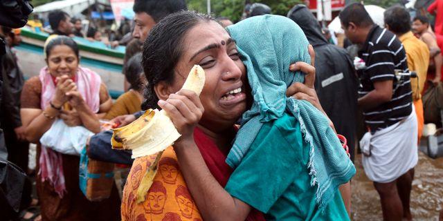 En kvinna håller om sitt barn efter att ha evakuerats från översvämningarna i Kerala. Sivaram V / TT NYHETSBYRÅN