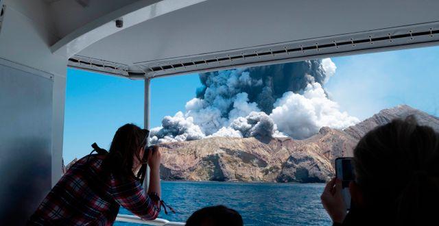 Turister blickar ut över vulkanön.  Michael Schade / TT NYHETSBYRÅN