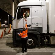 A man gives a document to the driver of the first truck, from Estonia, entering the Eurotunnel terminal Friday, Jan.1, 2021 in Coquelles, northern France. Eleven months after Britain's formal departure from the EU, Brexit becomes a fact of daily life on Friday, once a transition period ends and the U.K. fully leaves the world's most powerful trading bloc.  Lewis Joly / TT NYHETSBYRÅN