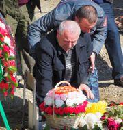 En man som förlorat sin son sitter och sörjer vid graven. TT NYHETSBYRÅN