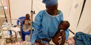 Jeanine Masika Mbuka Furana Katungu som själv överlevt ebola, vårdar en tvåårig ebolapatient. Baz Ratner / TT NYHETSBYRÅN