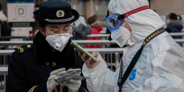 Säkerhetspersonal bär masker i Wuhan, den stad där smittan spridits ifrån. NICOLAS ASFOURI / AFP