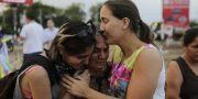 Mamman till en 16-årig pojke som dog under protesterna tröstas av närstående.  INTI OCON / AFP