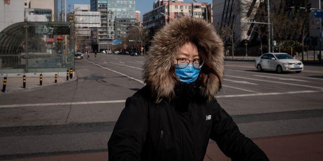 Kvinna i Peking på lördagen. NICOLAS ASFOURI / AFP