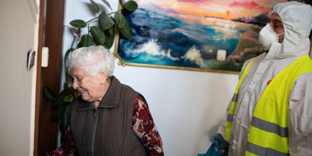 En hemtjänstarbetare i Aten hjälper 83-åriga Vassiliki Chalari med en matvaruleverans. ALKIS KONSTANTINIDIS / TT NYHETSBYRÅN