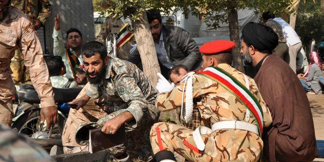 Soldater och civila tar skydd under beskjutningen. Behrad Ghasemi / TT NYHETSBYRÅN